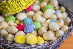 Το καλάθι με τα ξύλινα κομμάτια προς κατεργασία των αυγών Πάσχας, αυγά χρωμάτισε στα διαφορετικά χρώματα στοκ φωτογραφία