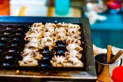 Το καλαμάρι Takoyaki ψήθηκε στη σχάρα και τηγανίστηκε στην καυτή σόμπα μετάλλων στοκ εικόνες