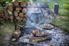 Το καλοκαίρι, ένα ψάρι είναι μαγειρευμένο σε μια πυρκαγιά σε έναν ακατέργαστο χυτοσίδηρο, και το ψάρι είναι Στοκ Εικόνες