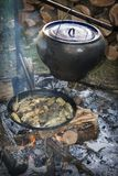 Το καλοκαίρι, ένα ψάρι είναι μαγειρευμένο σε μια πυρκαγιά σε έναν ακατέργαστο χυτοσίδηρο, και το ψάρι είναι Στοκ Φωτογραφίες
