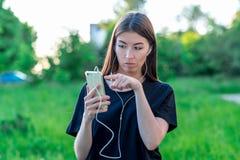 Το καλοκαίρι κοριτσιών brunette στη φύση πάρκων Ι ` μ που προσέχει σας Κρατά τα χέρια με ένα τηλέφωνο με τα ακουστικά Με τη χειρο Στοκ εικόνες με δικαίωμα ελεύθερης χρήσης