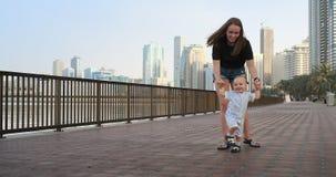 Το καλοκαίρι μια νέα μητέρα που περπατά με ένα παιδί κατά μήκος του περιπάτου φιλμ μικρού μήκους