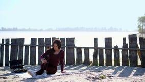 Το καλοκαίρι, στην όχθη ποταμού, στην παραλία ένας όμορφος καλλιτέχνης γυναικών κάθεται σε ένα κάλυμμα, στην άμμο, απολαμβάνοντας απόθεμα βίντεο