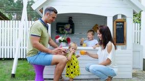 Το καλοκαίρι, στον κήπο, οι γονείς παίζουν με τα μικρά παιδιά, ένα κορίτσι και ένα αγόρι, σε έναν καφέ, σε ένα σπίτι παιχνιδιού π απόθεμα βίντεο