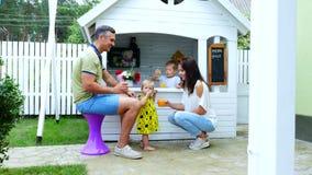 Το καλοκαίρι, στον κήπο, οι γονείς παίζουν με τα μικρά παιδιά, ένα κορίτσι και ένα αγόρι, σε έναν καφέ, σε ένα σπίτι παιχνιδιού π φιλμ μικρού μήκους