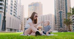 Το καλοκαίρι στο πάρκο mom ταΐζει το παιδί από το μεσημεριανό γεύμα εμπορευματοκιβωτίων απόθεμα βίντεο