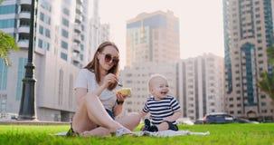 Το καλοκαίρι στο πάρκο mom ταΐζει το παιδί από το μεσημεριανό γεύμα εμπορευματοκιβωτίων φιλμ μικρού μήκους