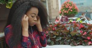 Το καλό αρκετά αφρικανικό κορίτσι βάζει στα ακουστικά, χαμόγελο, που απολαμβάνει τη μουσική κρατώντας το κινητό τηλέφωνο απόθεμα βίντεο