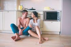 Το καλό ζεύγος κάθεται στο πάτωμα στην κουζίνα και εξετάζει το ένα το άλλο Κρατούν τα χέρια τους διασχισμένα Οι άνθρωποι χαμογελο στοκ φωτογραφίες