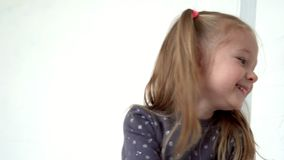 Το καλό κορίτσι με το uybatsya ουρών μπροστά από τη κάμερα Οι μικρές δαπάνες κοριτσιών χαμόγελου σε ένα άσπρο υπόβαθρο απόθεμα βίντεο