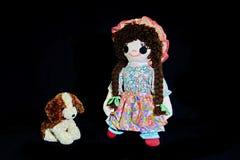 Το καλό κουτάβι, κάθεται Εκλεκτής ποιότητας κούκλα κουρελιών κοριτσιών με το κουτάβι της  παρουσιασμένος σε ένα σαφές μαύρο υπόβα στοκ εικόνες