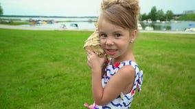 Το καλό μικρό κορίτσι ακούει ένα μεγάλο κοχύλι για να ακούσει το θόρυβο των κυμάτων κλείστε επάνω απόθεμα βίντεο