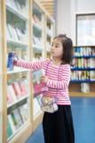 Το καλό μικρό κορίτσι διαβάζει στη βιβλιοθήκη στοκ φωτογραφία