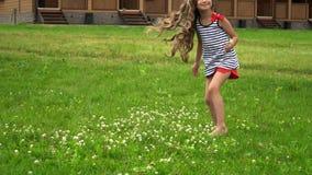 Το καλό μικρό κορίτσι στο πάρκο αναπηδά στη διαδρομή Το κορίτσι πηγαίνει στη κάμερα απόθεμα βίντεο