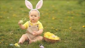 Το καλό μωρό σε ένα κοστούμι λαγουδάκι Πάσχας συλλέγει τα αυγά Πάσχας σε μια συνεδρίαση καλαθιών στη χλόη στο πάρκο Πικ-νίκ άνοιξ απόθεμα βίντεο