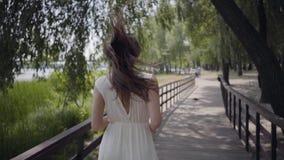 Το καλό νέο κορίτσι πορτρέτου με την τρίχα brunette που φορά τα γυαλιά ηλίου και η μακροχρόνια λευκιά θερινή μόδα ντύνουν το τρέξ απόθεμα βίντεο