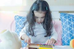 Το καλό παιχνίδι παιχνιδιού μικρών κοριτσιών στο κρεβάτι στην κρεβατοκάμαρα και το χαριτωμένο προσχολικού κορίτσι παιδιών ή τρώει στοκ εικόνα με δικαίωμα ελεύθερης χρήσης