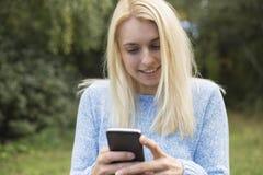 Το καλό χαμογελώντας κορίτσι διαβάζει sms στο κινητό τηλέφωνο, Στοκ εικόνες με δικαίωμα ελεύθερης χρήσης
