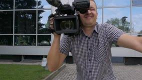 Το καμεραμάν κρατά βιντεοκάμερα στον ώμο του και πυροβολεί το βίντεο, που κινείται στο πλαίσιο απόθεμα βίντεο