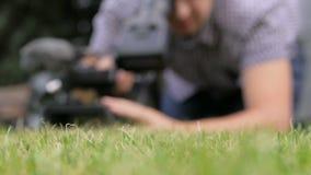 Το καμεραμάν που βρίσκεται στην πράσινη χλόη απόθεμα βίντεο