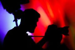 Το καμεραμάν, σκιαγραφία του ατόμου με τα βιντεοκάμερα Στοκ εικόνα με δικαίωμα ελεύθερης χρήσης