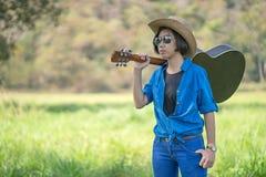 Το καπέλο ένδυσης γυναικών και φέρνει την κιθάρα της στον τομέα χλόης Στοκ Εικόνα