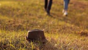 Το καπέλο που βρίσκεται στη χλόη, στα πλαίσια της διάβασης των προσώπων απόθεμα βίντεο