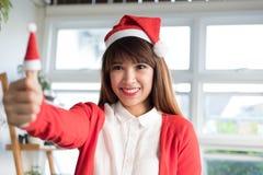 Το καπέλο santa ένδυσης γυναικών παρουσιάζει αντίχειρα ασιατικό θηλυκό άσπρο shi ένδυσης Στοκ φωτογραφία με δικαίωμα ελεύθερης χρήσης