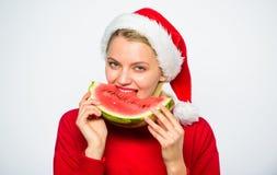 Το καπέλο santa κοριτσιών τρώει το άσπρο υπόβαθρο καρπουζιών Οι τρόποι απολαμβάνουν τα τροπικά Χριστούγεννα Εξωτικός εορτασμός Χρ στοκ φωτογραφία