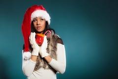 Το καπέλο αρωγών santa χειμερινών κοριτσιών κρατά την κόκκινη κούπα Στοκ φωτογραφίες με δικαίωμα ελεύθερης χρήσης