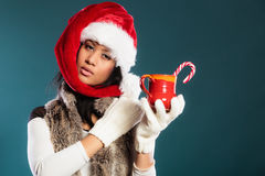 Το καπέλο αρωγών santa χειμερινών κοριτσιών κρατά την κόκκινη κούπα Στοκ εικόνες με δικαίωμα ελεύθερης χρήσης