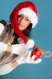 Το καπέλο αρωγών santa χειμερινών κοριτσιών κρατά την κόκκινη κούπα Στοκ Εικόνες
