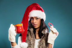 Το καπέλο αρωγών santa χειμερινών κοριτσιών κρατά την κόκκινη κούπα Στοκ φωτογραφία με δικαίωμα ελεύθερης χρήσης