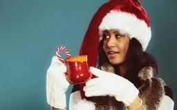 Το καπέλο αρωγών santa χειμερινών κοριτσιών κρατά την κόκκινη κούπα Στοκ Εικόνα