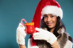 Το καπέλο αρωγών santa χειμερινών κοριτσιών κρατά την κόκκινη κούπα Στοκ εικόνα με δικαίωμα ελεύθερης χρήσης
