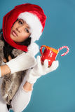 Το καπέλο αρωγών santa χειμερινών κοριτσιών κρατά την κόκκινη κούπα Στοκ Φωτογραφία