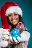 Το καπέλο αρωγών santa χειμερινών κοριτσιών κρατά την μπλε κούπα Στοκ φωτογραφία με δικαίωμα ελεύθερης χρήσης