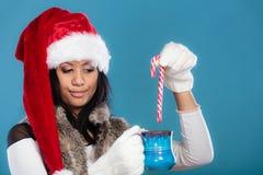Το καπέλο αρωγών santa χειμερινών κοριτσιών κρατά την μπλε κούπα Στοκ Εικόνα