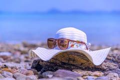 Το καπέλο και Sunglass στην ξυλεία η παραλία χαλαρώνουν την έννοια διακοπών θερινών διακοπών που τονίζεται Στοκ Εικόνες