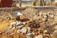 Το καροτσάκι, το φτυάρι, το κοίλωμα, η άμμος, οι πέτρες και το έδαφος κοντά στο κτήριο είναι κάτω από την οικοδόμηση με το νέο ίδ Στοκ Εικόνες