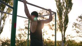 Το κατάλληλο μυϊκό άτομο στο μαύρο πουκάμισο που κάνει το τράβηγμα-UPS στο φραγμό οριζόντων στο χώρο αθλήσεων με τα δέντρα και το απόθεμα βίντεο