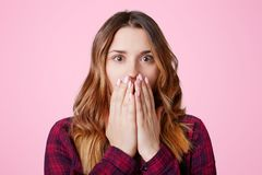 Το κατάπληκτο φοβησμένο νέο όμορφο θηλυκό που ντύνεται στο ελεγμένο πουκάμισο, καλύπτει το στόμα με τα χέρια, που συγκλονίζονται  στοκ εικόνες με δικαίωμα ελεύθερης χρήσης