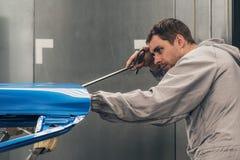 Το κατάστημα ζωγραφικής σωμάτων αυτοκινήτων υπαλλήλων αποβάλλει μια μικρή ατέλεια μετάλλων στοκ φωτογραφία με δικαίωμα ελεύθερης χρήσης