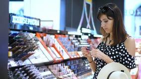 Το κατάστημα καλλυντικών, όμορφο brunette, μια γυναίκα εξετάζει προσεκτικά, επιλέγει τα καλλυντικά προϊόντα Πορτρέτο του νέου χαμ απόθεμα βίντεο