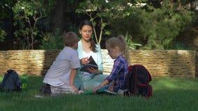 Το κατώτερο σχολείο, η ενεργοί μαθήτρια και ο μαθητής με τη γυναίκα εκπαιδευτικών διαβάζουν τα βιβλία και τη συνομιλία κατά τη δι απόθεμα βίντεο