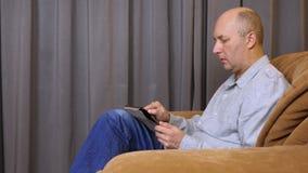 Το καυκάσιο άτομο γράφει με το δάχτυλο στην ταμπλέτα Το άτομο κάθεται στην πολυθρόνα φιλμ μικρού μήκους