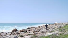 Το καυκάσιο αθλητικό άτομο τρέχει και πηδά πέρα από τους βράχους κατά μήκος της παραλίας σε αργή κίνηση φιλμ μικρού μήκους