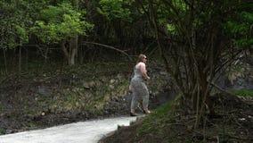 Το καυκάσιο θηλυκό περπατά επάνω τον πρόσφατα τσιμενταρισμένο λόφο μέσω των δέντρων απόθεμα βίντεο