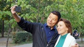 Το καυκάσιο κορίτσι και το ασιατικό αγόρι παίρνουν μια φωτογραφία με το smartphone Selfie σε ένα ηλιόλουστο πάρκο απόθεμα βίντεο