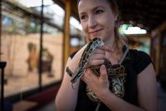 Το καυκάσιο κορίτσι κρατά το φίδι στο πάρκο άγριας φύσης Langkawi στοκ εικόνες